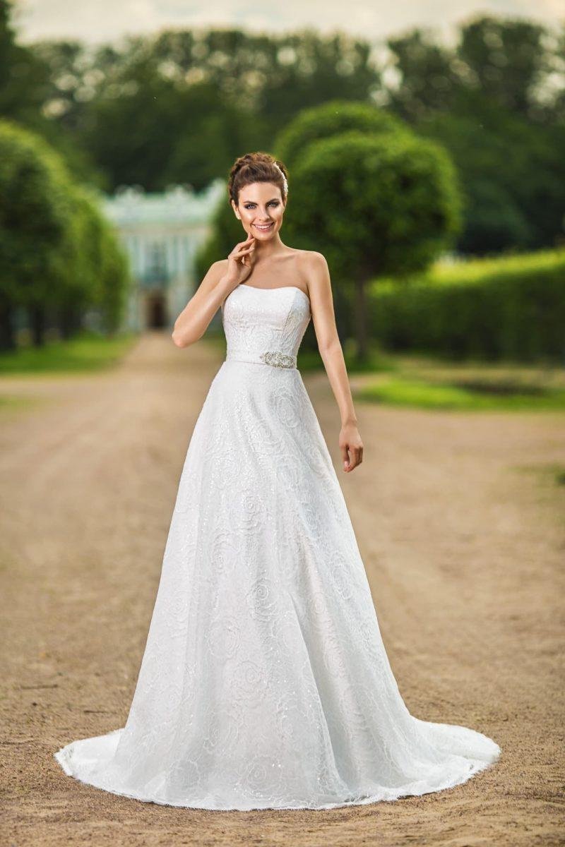 Прямое свадебное платье из фактурной ткани с поясом на талии и длинным шлейфом.