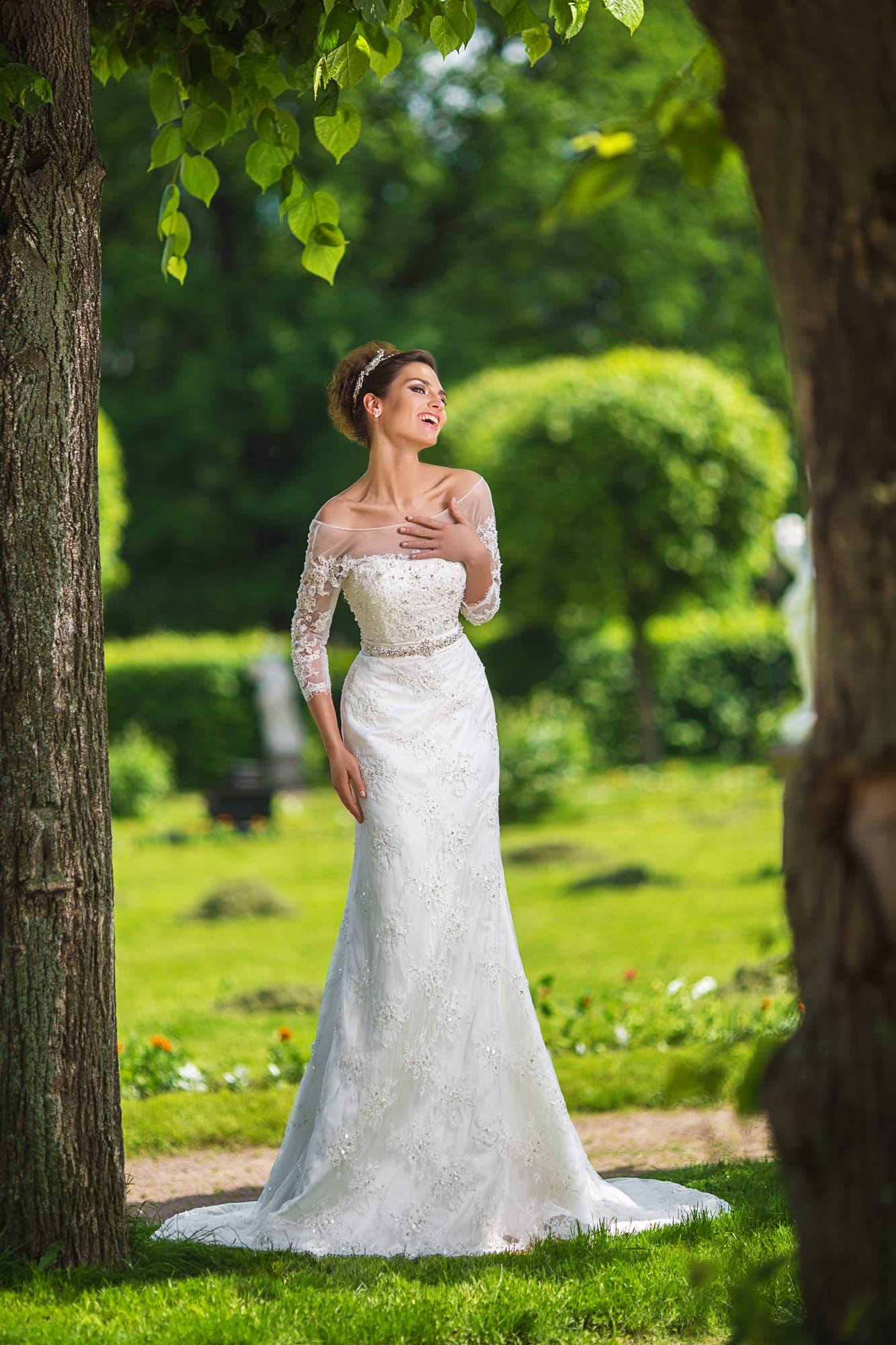 Прямое свадебное платье с портретным декольте и длинным рукавом из тонкой ткани.