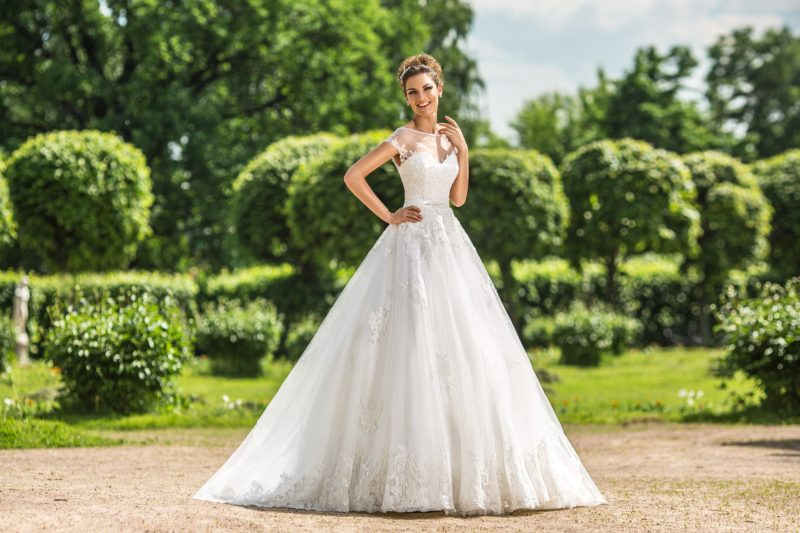 Пышное свадебное платье с полупрозрачной отделкой корсета и узким поясом на талии.