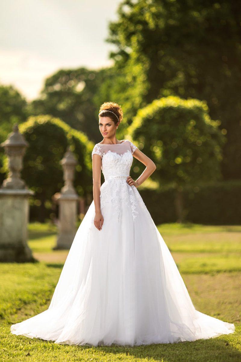 Пышное свадебное платье с многослойной юбкой и закрытым верхом с округлым вырезом.