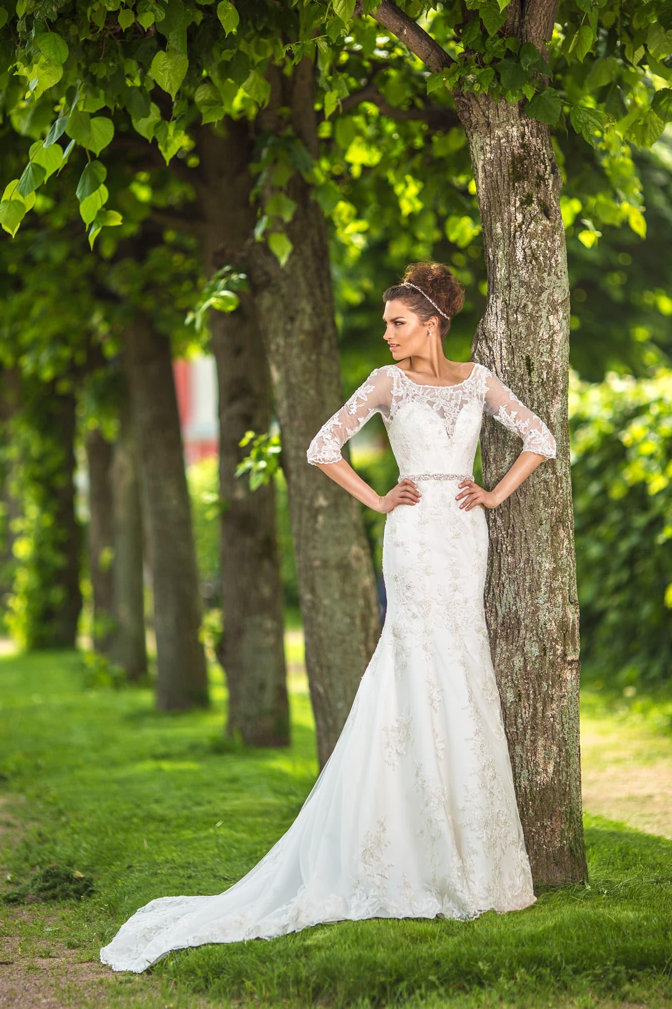 Прямое свадебное платье с роскошным шлейфом и ажурными рукавами длиной до локтя.