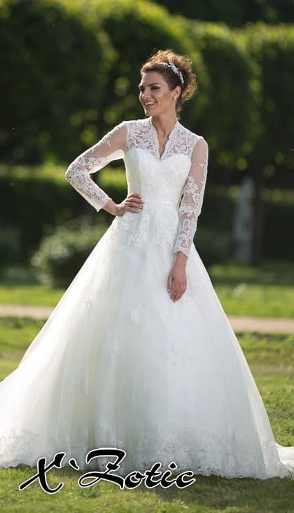 Сдержанное свадебное платье силуэта «принцесса» с V-образным вырезом и длинными рукавами.