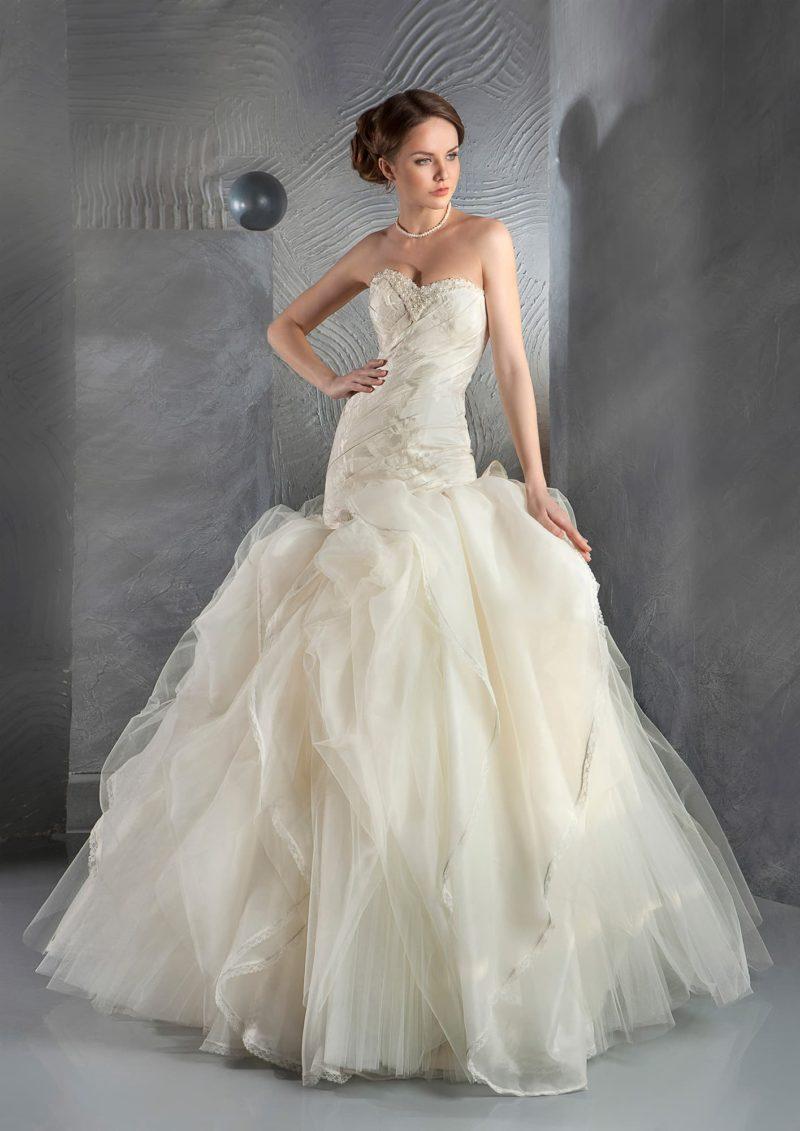 Свадебное платье цвета слоновой кости с пышной юбкой силуэта «рыбка» из тонкой ткани.