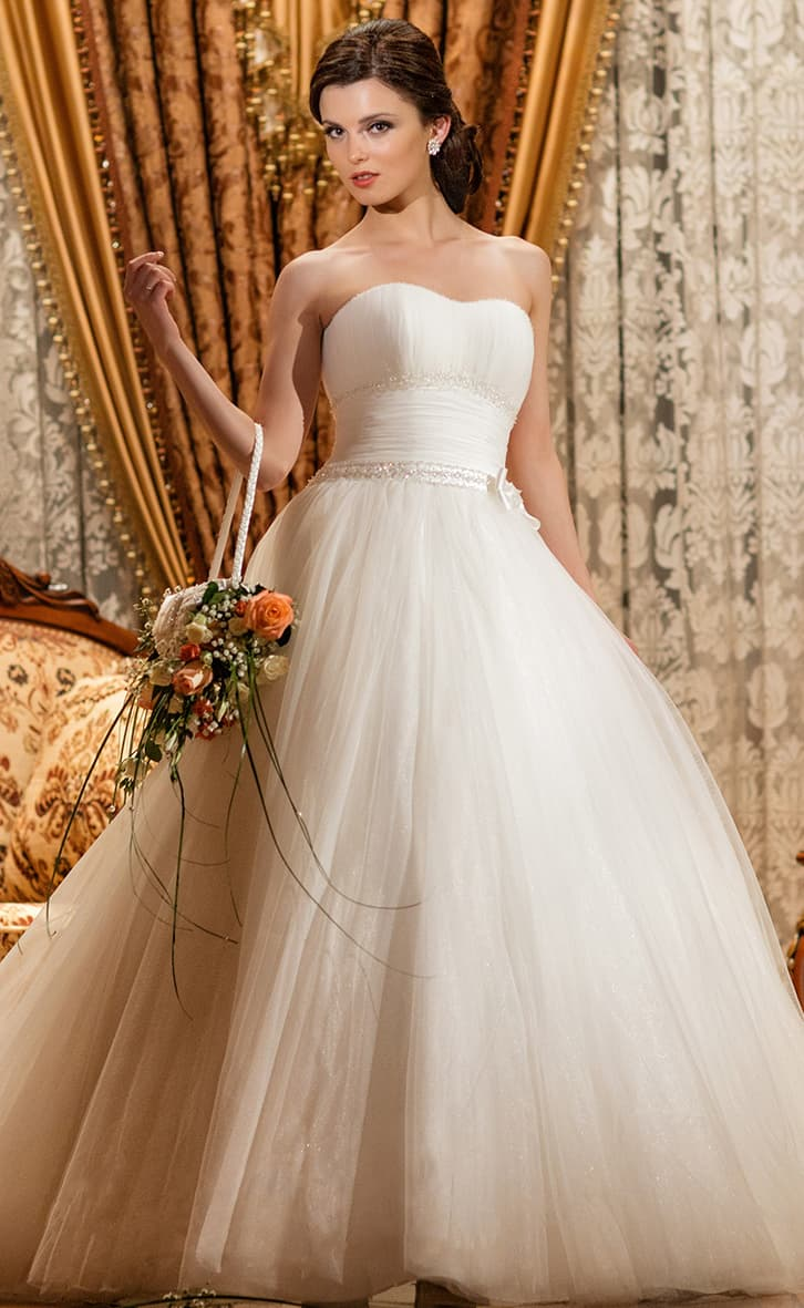 Открытое свадебное платье пышного силуэта с лаконичным декором из драпировок.