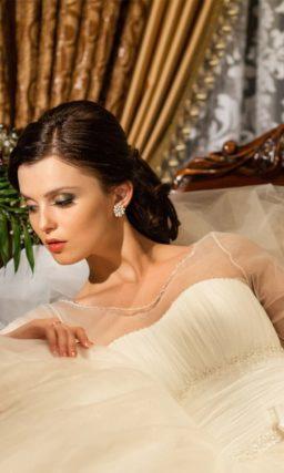 Закрытое свадебное платье с длинным полупрозрачным рукавом.