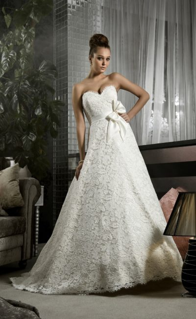 Атласное свадебное платье силуэта «принцесса» с кружевным декором и широким поясом.