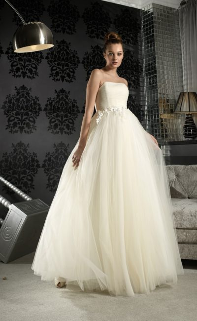 Пышное свадебное платье цвета слоновой кости с объемными бутонами по поясу.