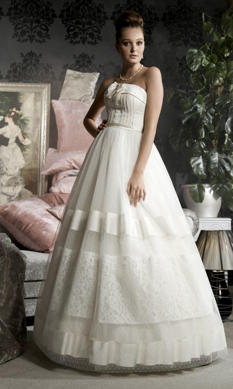 Свадебное платье «принцесса» с декором из атласных полос по подолу и открытым корсетом.