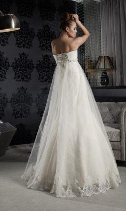 Прямое свадебное платье с завышенной линией талии и полупрозрачным верхом по юбке.