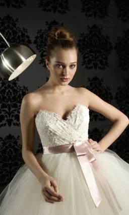 Открытое свадебное платье пышного силуэта с оборками на юбке и широким цветным поясом.