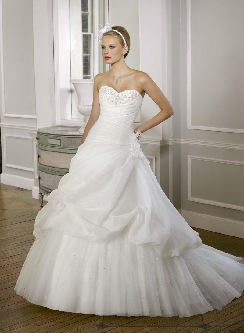 Пышное свадебное платье с бисерной вышивкой на лифе и оборками на юбке.