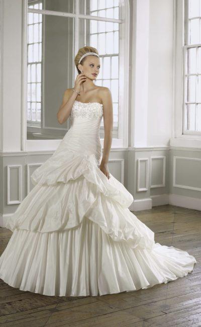 Пышное свадебное платье со сложной многоярусной юбкой со шлейфом.