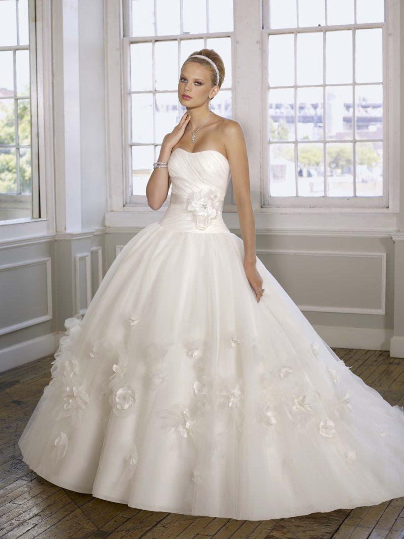 Открытое свадебное платье пышного силуэта с декором из объемных бутонов.