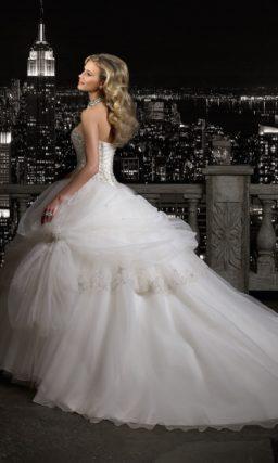 Пышное свадебное платье с длинным шлейфом и корсетом, полностью покрытым бисером.
