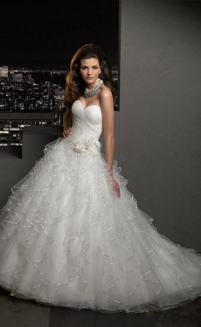 Пышное свадебное платье с полупрозрачными оборками на подоле, украшенными тесьмой.