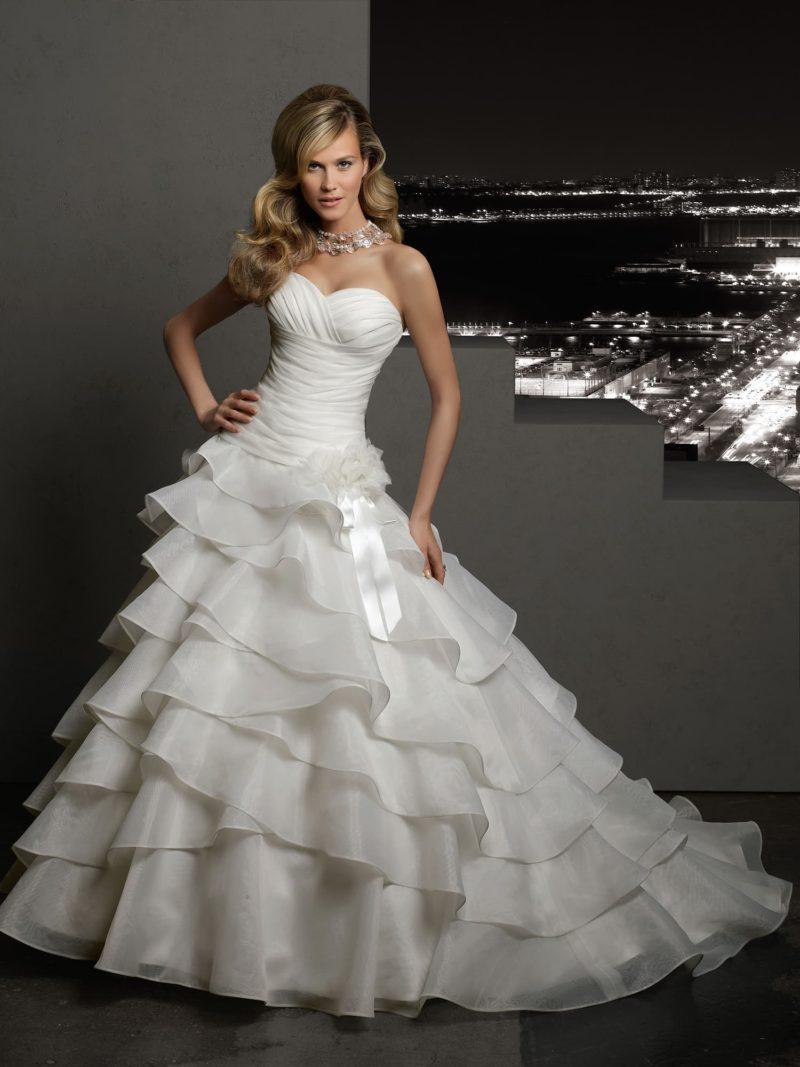 Открытое свадебное платье с отделкой из пышных оборок на юбке.