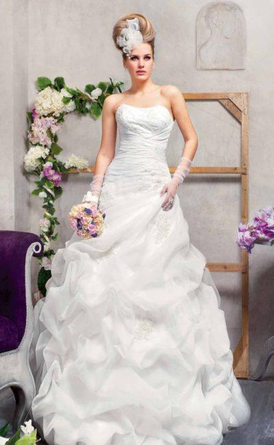Открытое свадебное платье силуэта «принцесса» с эксцентричным декором из оборок.