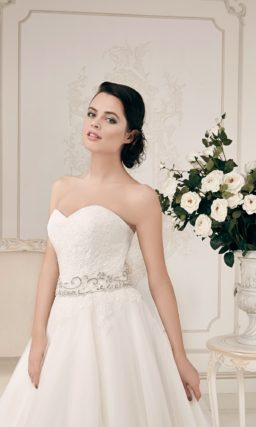 Открытое свадебное платье силуэта «принцесса» с бисерным поясом и кружевной отделкой юбки.