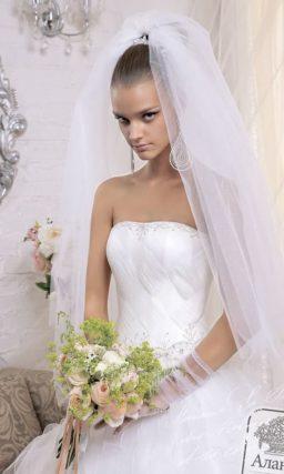 Пышное свадебное платье с невероятно торжественной юбкой, покрытой асимметричными волнами.