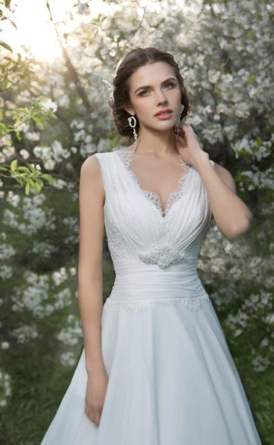 Элегантное свадебное платье прямого силуэта с V-образным лифом, украшенным по краю кружевом.