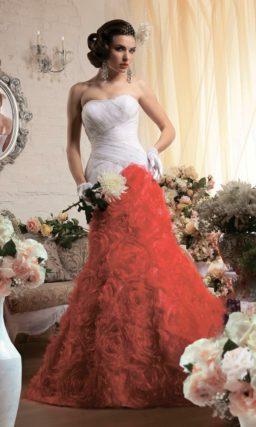 Свадебное платье «рыбка» с белым корсетом и красной юбкой, покрытой пышными бутонами.