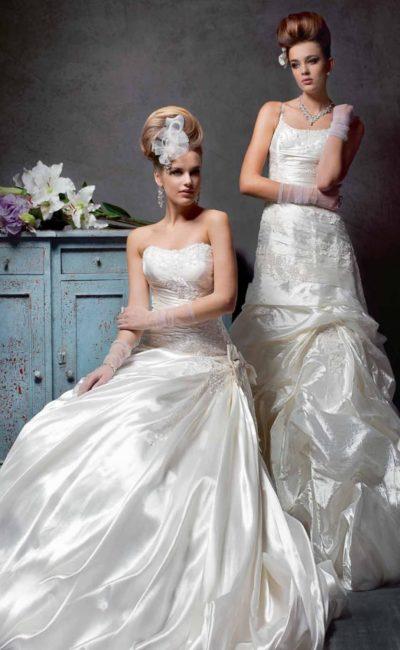 Открытое свадебное платье из роскошной глянцевой ткани с множеством драпировок.