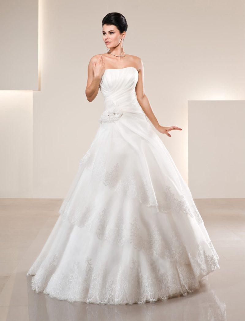 Открытое свадебное платье «принцесса» с прямым лифом и кружевными оборками по подолу.