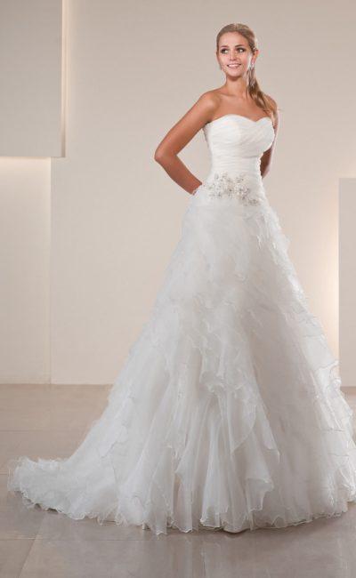 Романтичное свадебное платье с драпировками на лифе и пышной отделкой юбки со шлейфом.