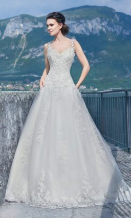 Ажурное свадебное платье с многослойной юбкой А-силуэта и узкими фигурными бретелями.
