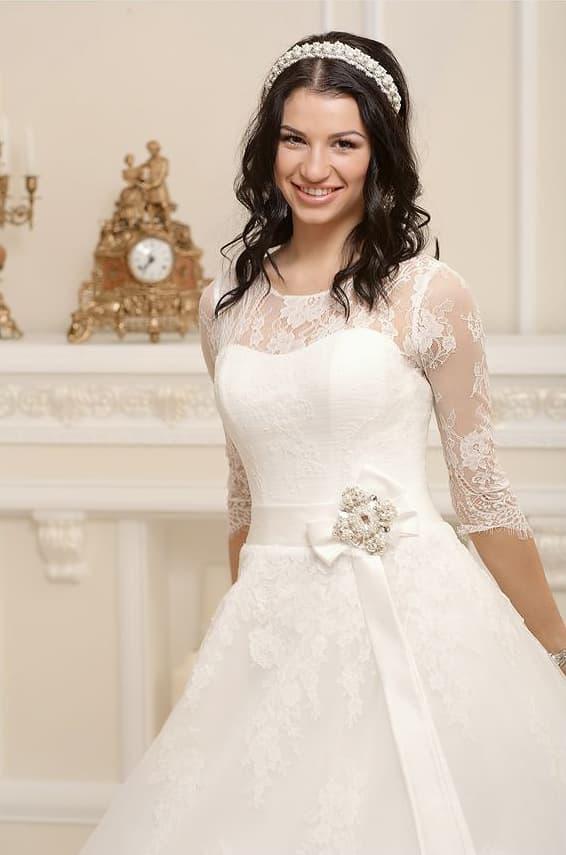 Закрытое свадебное платье с кружевным рукавом в три четверти и широким поясом.
