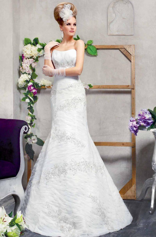Свадебное платье силуэта «рыбка», от открытого лифа до подола покрытое полосами вышивки.