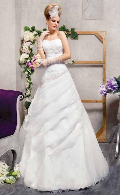 Свадебное платье с юбкой А-силуэта, покрытой драпировками полупрозрачной ткани.