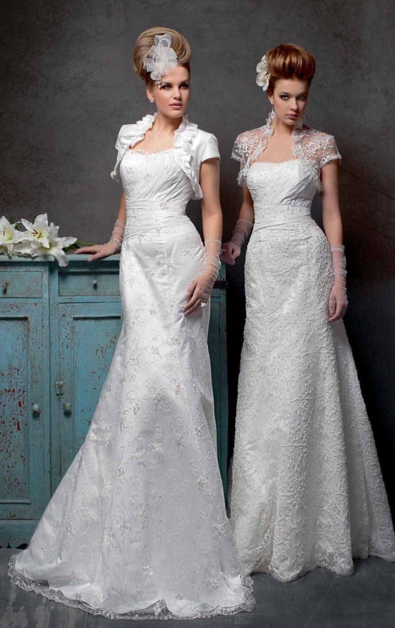 Прямое свадебное платье с открытым лифом, декорированное драпировками и кружевом.