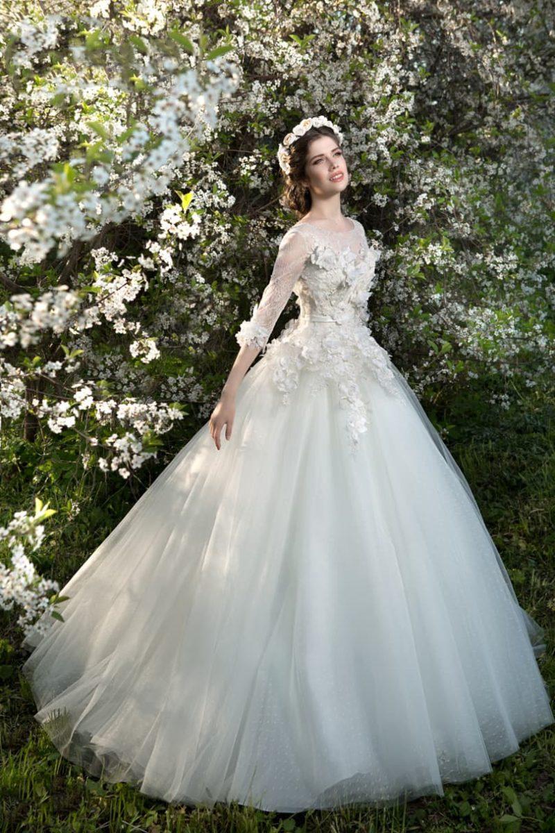 Пышное свадебное платье с длинными ажурными рукавами и объемным декором корсета.