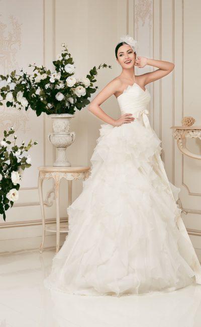 Пышное свадебное платье с асимметричным лифом и оборками на подоле.