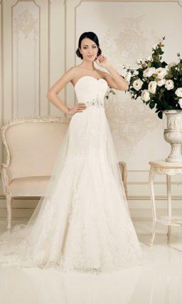 Открытое свадебное платье силуэта «рыбка» с полупрозрачной верхней юбкой и поясом.