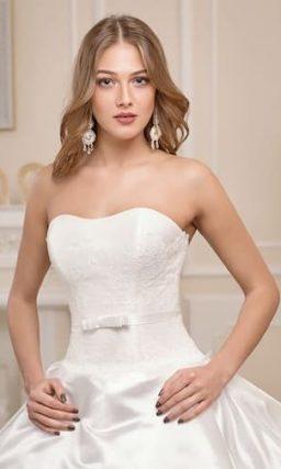 Пышное свадебное платье с роскошной отделкой юбки и узким поясом на талии.