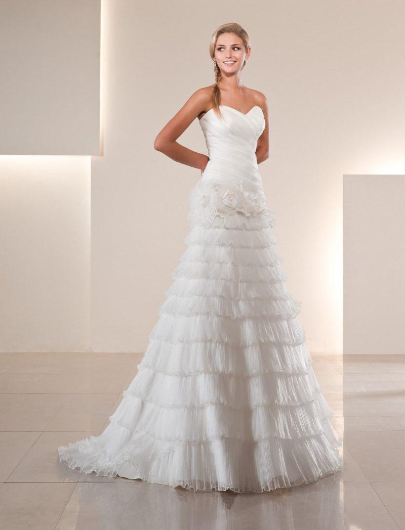 Кокетливое свадебное платье силуэта «принцесса» с множеством горизонтальных оборок на юбке.