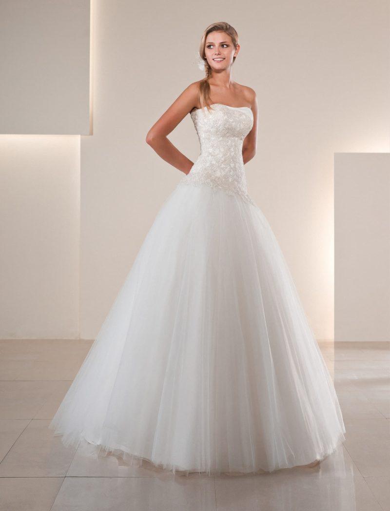 Пышное свадебное платье с многослойной юбкой и кружевным декором корсета.