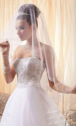 Пышное свадебное платье с фактурным корсетом и объемной отделкой многослойной юбки.