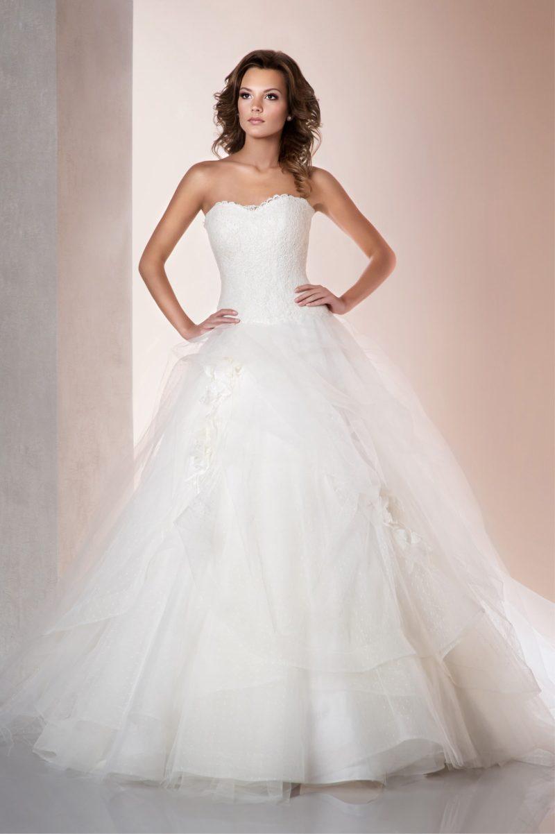 Пышное свадебное платье с классическим корсетом и роскошными волнами ткани на подоле.