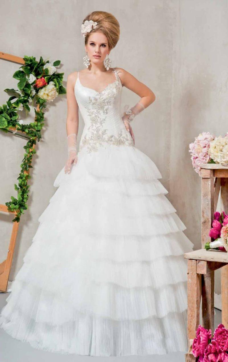 Пышное свадебное платье с вышивкой на корсете и многоярусной юбкой из полупрозрачной ткани.