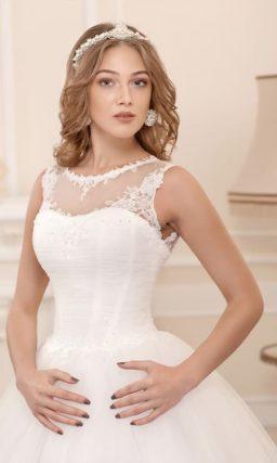 Пышное свадебное платье с закрытым лифом и объемной отделкой по нижней части подола.