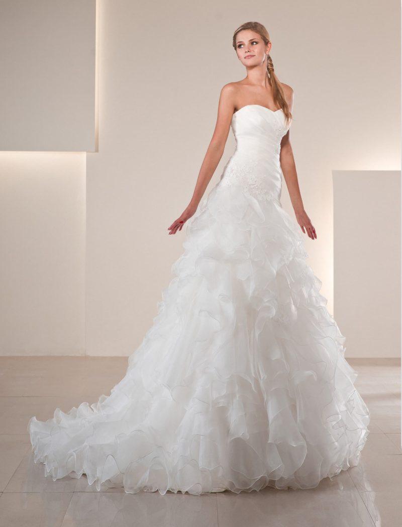 Прямое свадебное платье с юбкой, покрытой полупрозрачными оборками и украшенной шлейфом.