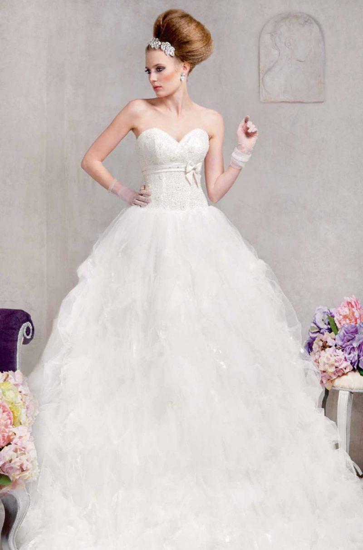 Пышное свадебное платье с глубоким декольте в форме сердца и атласным поясом с бантом.