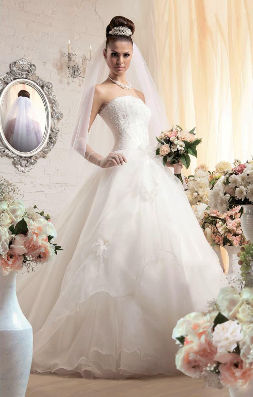 Стильное свадебное платье пышного силуэта с оборками и объемными бутонами на юбке.