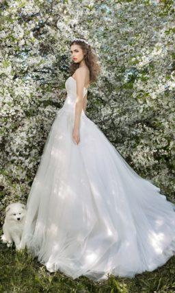 Открытое свадебное платье силуэта «принцесса» с длинным шлейфом и кружевным корсетом.