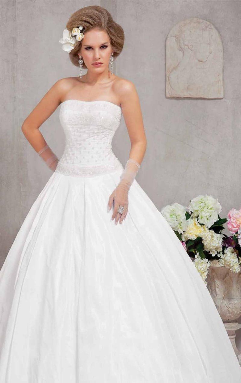 Пышное свадебное платье с открытым лифом, украшенным фактурной вышивкой.