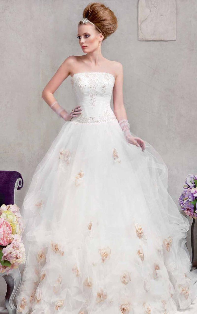 Романтичное свадебное платье с пышным силуэтом, украшенным цветными бутонами на юбке.