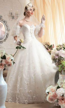 Пышное свадебное платье с открытым лифом, драпировками на корсете и вышивкой по подолу.